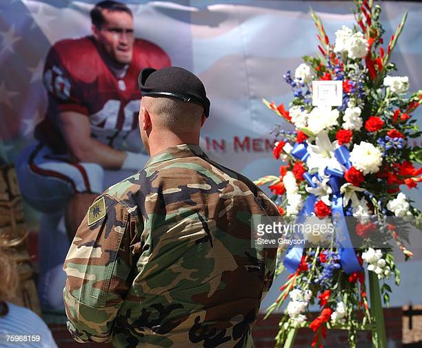 A member of the United States Armed Forces walks past a wreath and poster of Pat Tillman entering the memorial services for the exNFL player and Army...