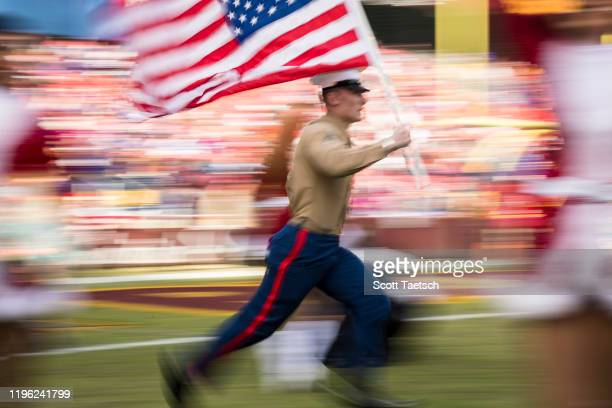 A member of the United States Marine Corps carries the US Flag before the game between the Washington Redskins and the New York Giants at FedExField...