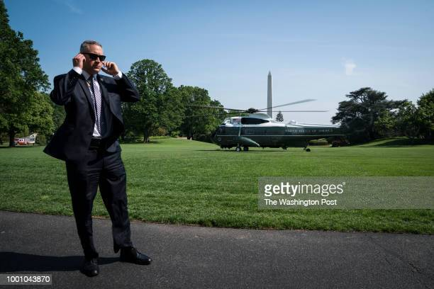 A member of the United States Secret Service stands guard as the Marine One helicopter carrying President Donald J Trump departs heading to Walter...