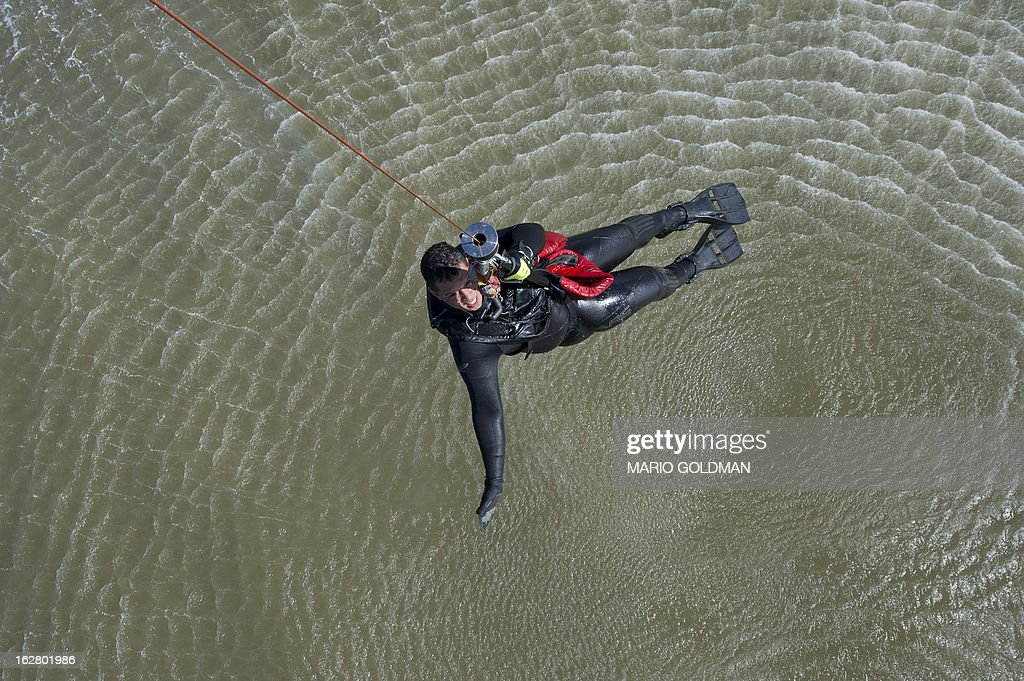 A member of the Uruguayan Air Force Operations, Training and Rescue Unit takes part in a drill at a beach of Salinas, near Montevideo, Uruguay on February 27, 2013. AFP PHOTO/Mario Goldman