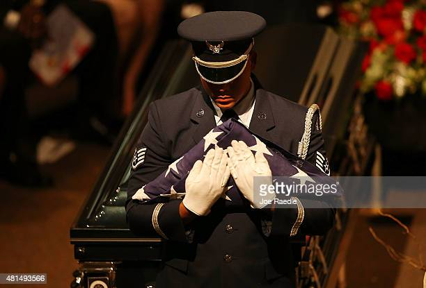 A member of the US Air Force 482nd Fighter Wing Honor Guard prepares to deliver the American flag to a family member during the funeral of retired...