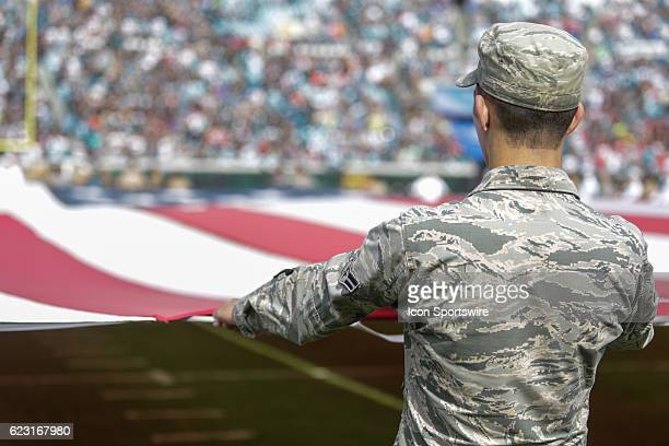 A member of the US Air Force holds the America flag during the national anthem during the NFL game between the Houston Texans and the Jacksonville...