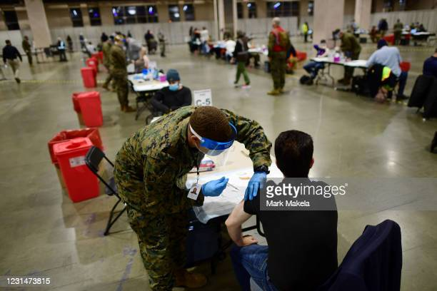 Member of the U.S. Armed Forces administers a COVID-19 vaccine at a FEMA community vaccination center on March 2, 2021 in Philadelphia, Pennsylvania....