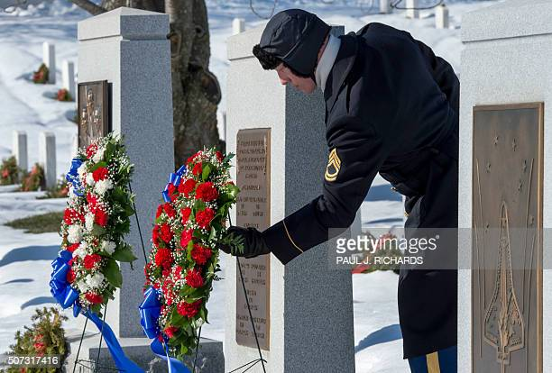 A member of the US Army Honor Guard adjusts the wreaths at the memorial site crew of the Space Shuttle Challenger during rememberance ceremonies for...