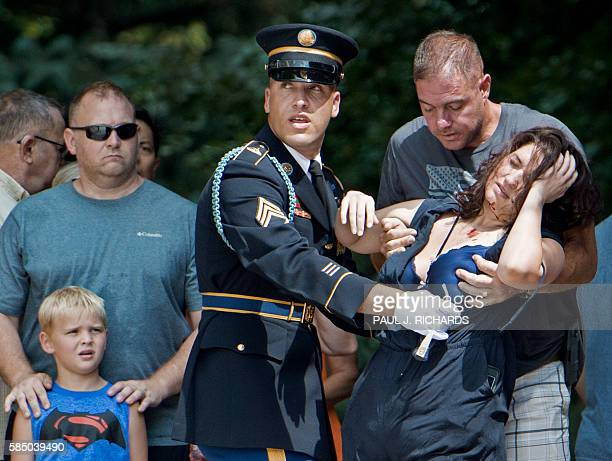 A member of the US Army Honor Guard and an unidentified man assist a unidentified woman who collapsed in the high heat and humidity during a wreath...