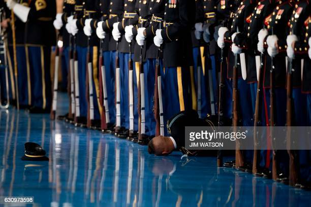 A member of the US Army Honor Guard lays on the floor after passing out during an Armed Forces Full Honor Farewell Review for US President Barack...
