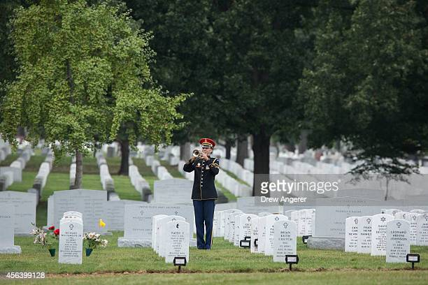 A member of the US Army Old Guard plays the bugle during the burial service for US Army Maj Michael Donahue at Arlington National Cemetery September...