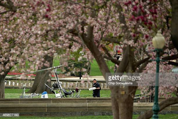 A member of the US Capitol Police Bomb Squad works to check and secure a gyrocopter that landed on the West Front of the US Capitol April 15 2015 in...
