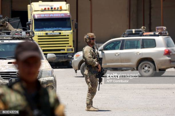 A member of the US forces stands guard during a meeting between US special Presidential Envoy for the Global Coalition to Counter IS and the Tabqa...