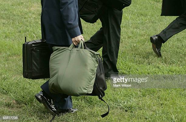 A member of the US military carries the football the case in his left hand as he walks behind US President George W Bush toward Marine One on the...
