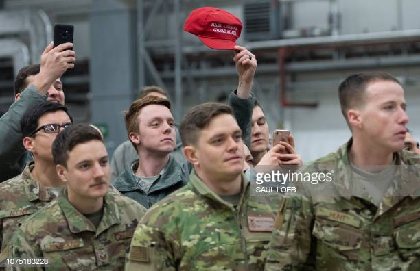 A member of the US military holds up a Make America Great Again hat as US President Donald Trump and First Lady Melania Trump greet members of the US...