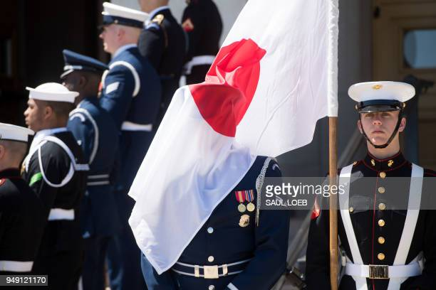 A member of the US Military Honor Guard is draped with the Japanese flag as they await the arrival of Japanese Defense Minister Itsunori Onodera for...