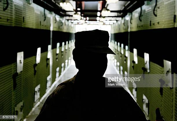 A Member of the US Military is silhouetted while standing inside of the cell block inside of Camp 2 at Camp Delta May 9 2006 in Guantanamo Bay Cuba...