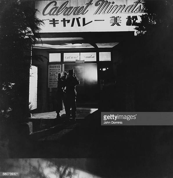 A member of the US Military Police inspects a GI entering the Cabaret Mimatsu in the Ginza Tokyo during the Allied occupation of Japan after World...
