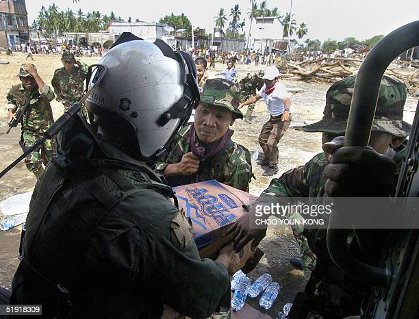 Member of the US Navy gives food and water supplies to refugees and local military at a devastated village, near Meulabo, in Teunom, 170 kms...
