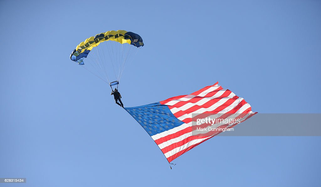 A member of the U.S. Navy Parachute Team, the Leap Frogs, holds an American Flag as he parachutes into the stadium prior to the SiriusXM All-Star Futures Game at PETCO Park on July 10, 2016 in San Diego, California.