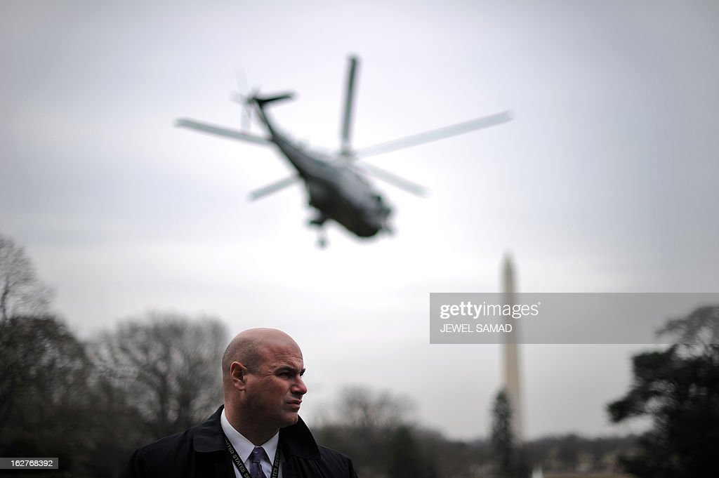 A member of the US Secret Service guards as Marine One helicopter with US President Barack Obama takes off on February 26, 2013 from White House in Washington, DC. Obama will Tuesday paint a devastating picture of looming government budget cuts, at a fabled shipbuilding yard in Virginia that provides the US Navy's nuclear powered aircraft carriers. AFP PHOTO/Jewel Samad