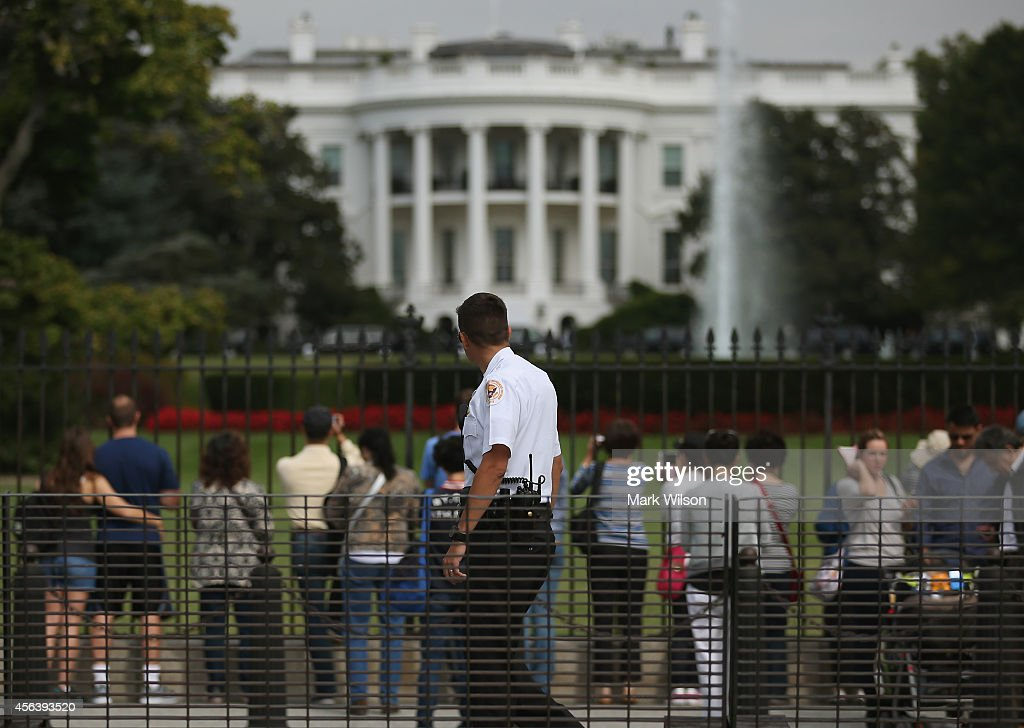 A member of the US Secret Service watches as tourist visit the south side of the White House September 30, 2014 in Washington, DC. White House intruder Omar Gonzalez, the man arrested last week after jumping the White House fence, went deeper into the building than what was previously reported.