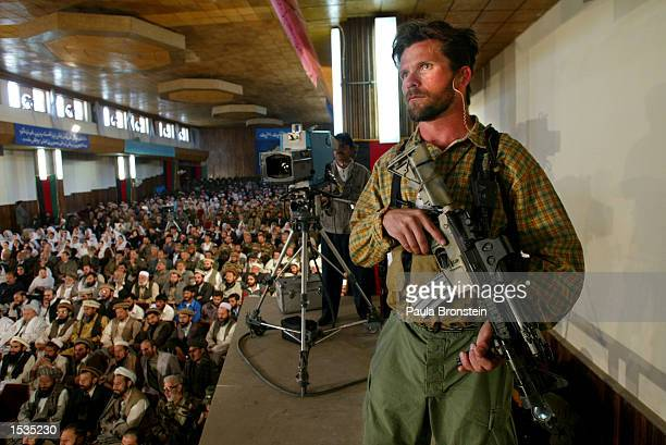 A member of the US Special Forces stands guard as Afghan President Hamid Karzai speaks during a memorial ceremony on the anniversary of the death of...