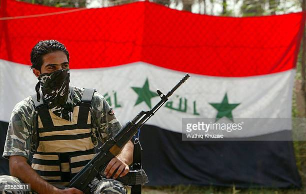 A member of the USbacked Neighborhood Patrol Awakening Council stands guard in front of an Iraqi flag on August 28 2008 in the Sunni Adhamiya...