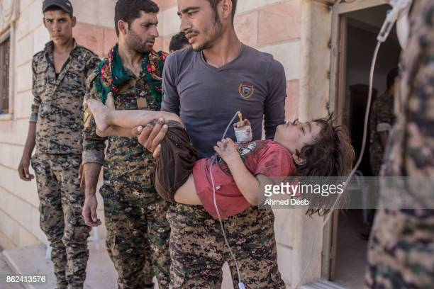 Member of the US-backed Syrian Democratic Forces holds a girl who was injured by a mine which exploded when a group of civilians were escaping the...