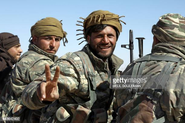 TOPSHOT A member of the USbacked Syrian Democratic Forces made up of an alliance of Arab and Kurdish fighters flashes the sign for victory in the...