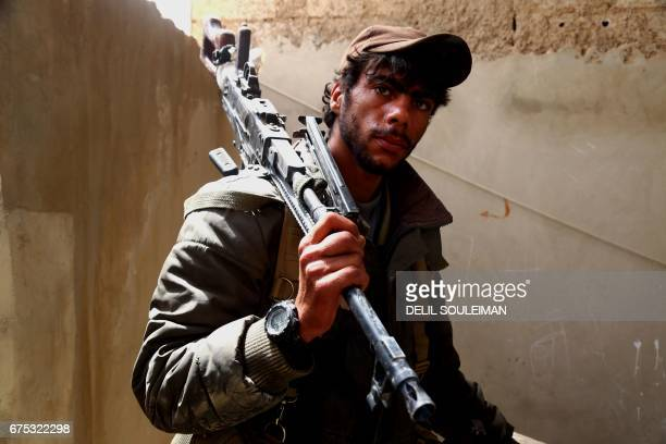 TOPSHOT A member of the USbacked Syrian Democratic Forces made up of an alliance of Arab and Kurdish fighters looks on in the town of Tabqa about 55...