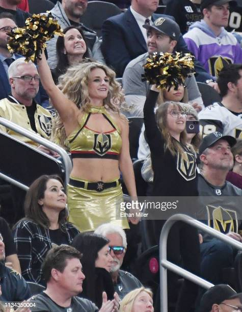A member of the Vegas Golden Knights Golden Aces cheers with a fan during the Knights' game against the Calgary Flames at TMobile Arena on March 6...
