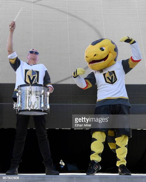 A member of the Vegas Golden Knights Knight Line Drumbots and the Vegas Golden Knights mascot Chance the Golden Gila Monster perform during a Vegas...