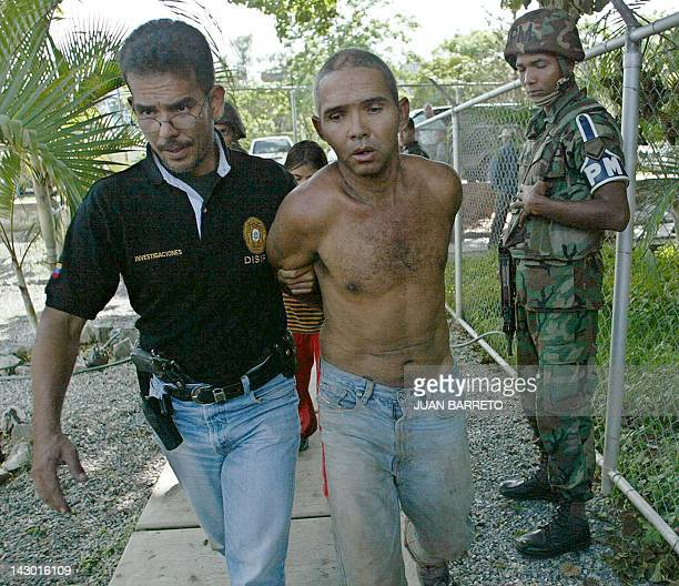 Member of the Venezuelan Intelligence and Prevention General Direction walks with an alleged Colombian paramilitary militant, in Caracas, after his...