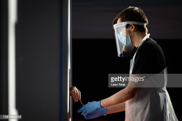 Member of the volunteer health worker team collects a used swab from a person within a privacy booth at a temporary COVID-19 testing centre at The...