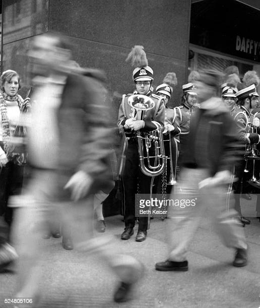 A member of the Wauwatosa Wisconsin High School marching band waits on a corner of Madison avenue for the 244th Annual St Partrick's Day Parade to...