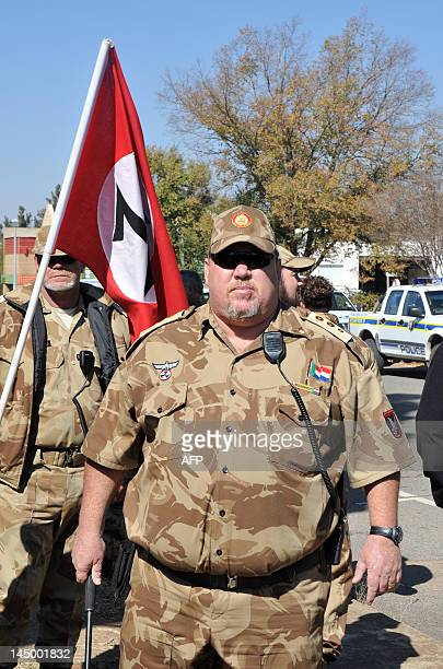 A member of the white supremacist Afrikaner Resistance Movement stands outside the Ventersdorp Magistrate court on May 22 2012 before the verdict of...