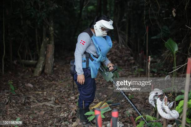 Member of the women demining team demonstrates how mines are unearthed by hand in a search for explosive ordnances at the southern Colombian jungle...