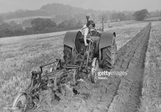 Member of the Women's Land Army ploughing furrows in a field with a tractor at the Gloucester and District Ploughing Society Ploughing match on 30th...