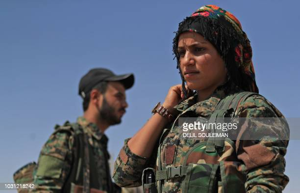 A member of the Women's Protection Units part of the of the Syrian Democratic Forces lines up while gathering in the town of Shadadi about 60...