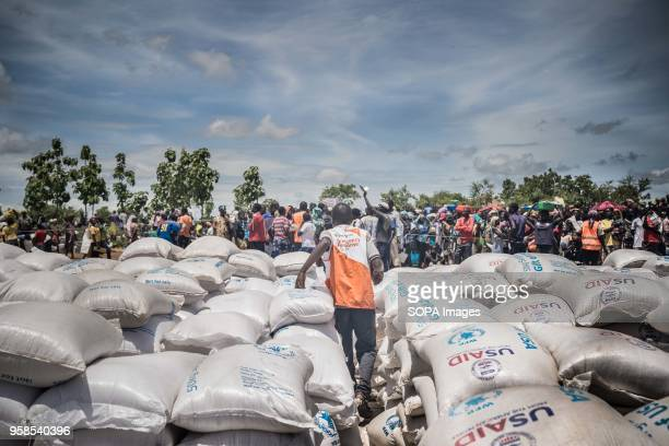 A member of the world vision team which responsible to the food distribution rushing to the crowd of refugees through piles of food supplies as a...