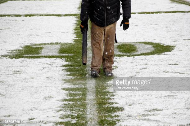 Member of the Yankee Stadium grounds crew clears snow from the 10-yard line before the New Era Pinstripe Bowl between West Virginia Mountaineers and...