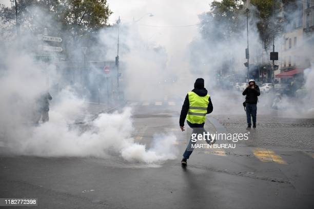 """Member of the """"yellow vest"""" movement kicks a tear gas canister as a photogapher takes pictures near the Porte de Champerret in Paris on November 16..."""