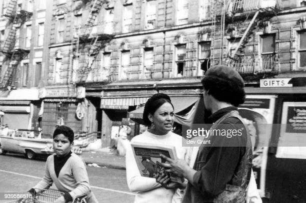 Member of the Young Lords Party member offers copies of the party's newspaper, Palante, to a woman on an East Harlem sidewalk, New York, New York,...