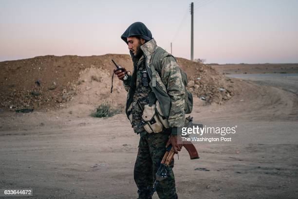 A member of the YPG uses a radio in a village close to the frontline in Tal Samin Syria during the operation to isolate Raqqa city