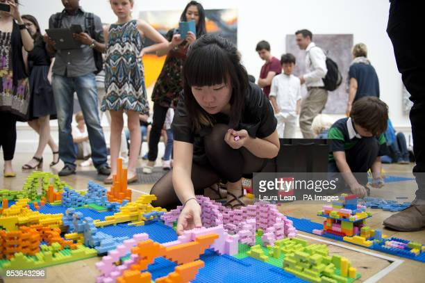 A member of the Zaha Hadid Architects team works on their design at the UK's first Lego battle inside the Royal Academy's Summer Exhibition Central...