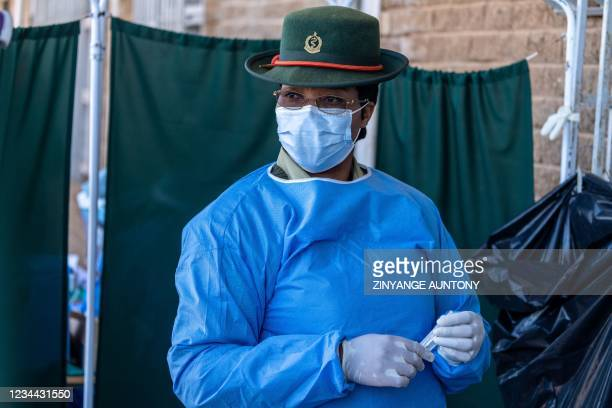 Member of the Zimbabwe National Army holds a syringe awaiting to jab a dose of the SinoVac vaccine during the Defence Forces week long community...