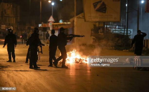 Member of Tunisian security forces aims his gun after protesters set tires and garbage containers on fire to protest against price hikes at...