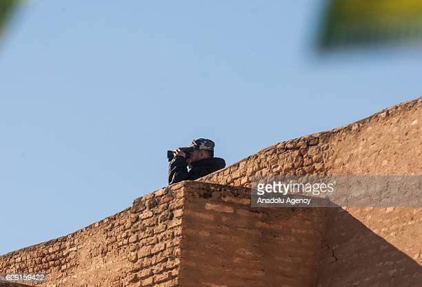 A member of Tunisian security forces looks through binoculars as Muslims on their way to the Great Mosque of Kairouan also known as the Mosque of...