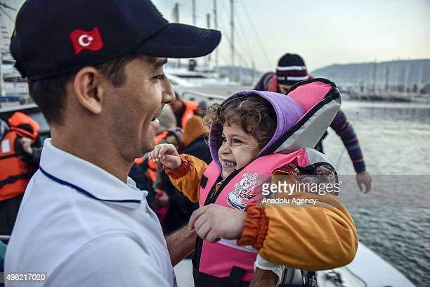 A member of Turkish coast guard holds a refugee kid after 82 refugees of Syrian Afghan and Myanmar origin trying to reach Greece's Kos island were...