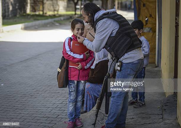 A member of Turkish security forces talks to a little girl as Turkish Special Operation Forces carry out an operation against PKK terrorist...
