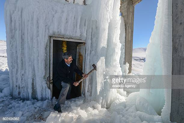 A member of Van Water and Sewerage Administration team breaks the ice around a water tank which exploded after the pipes on the feeder froze because...