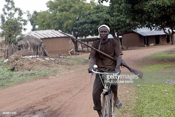 A member of vigilante group in Sabon Gida patrols the town with his locally produced hunting riffle gun on his bicycle 21 May 2004 following attacks...