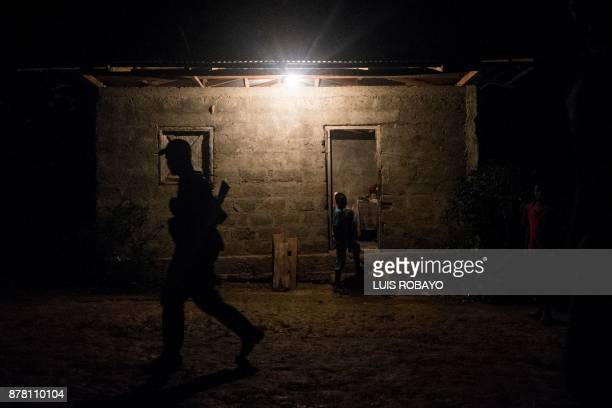 A member of Western Front of War Omar Gomez of the National Liberation Army guerrilla walks in front of houses on November 20 2017 in banks of the...